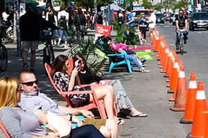 People relaxing in chairs on Queen St W.